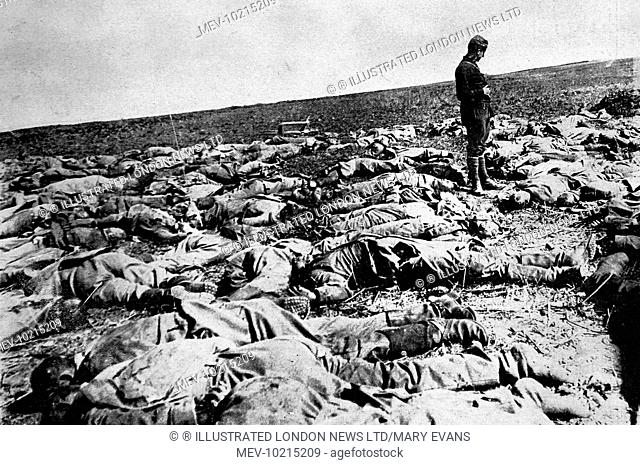 A French soldier standing amidst German dead killed while attempting to storm the French lines between Soissons and Berry-au-Bac