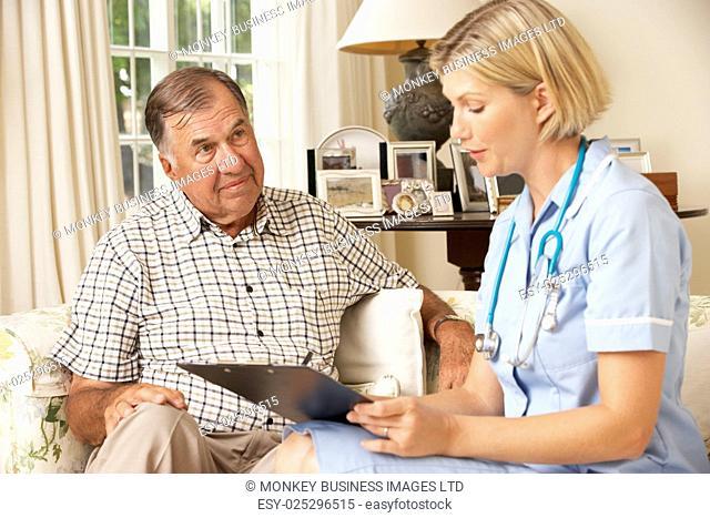 Retired Senior Man Having Health Check With Nurse At Home