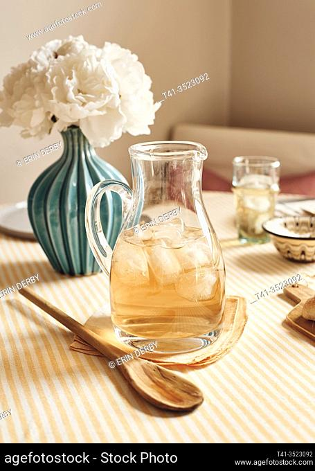 A pretty table setting in a kitchen, dressed up for brunch or a party, with a pitcher of iced tea