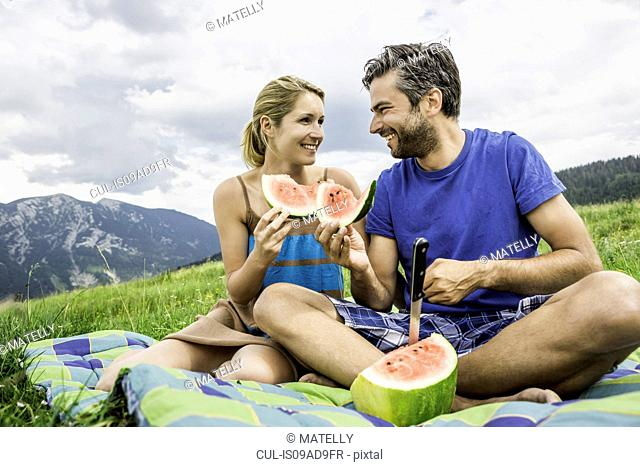 Couple eating watermelon at picnic