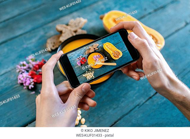 Close-up of man's hands taking picture of creamed pumpkin soup with smartphone