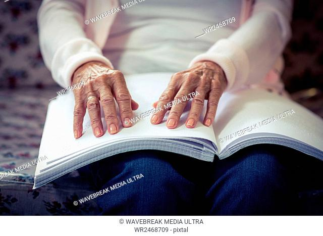Blind woman reading a braille book at home