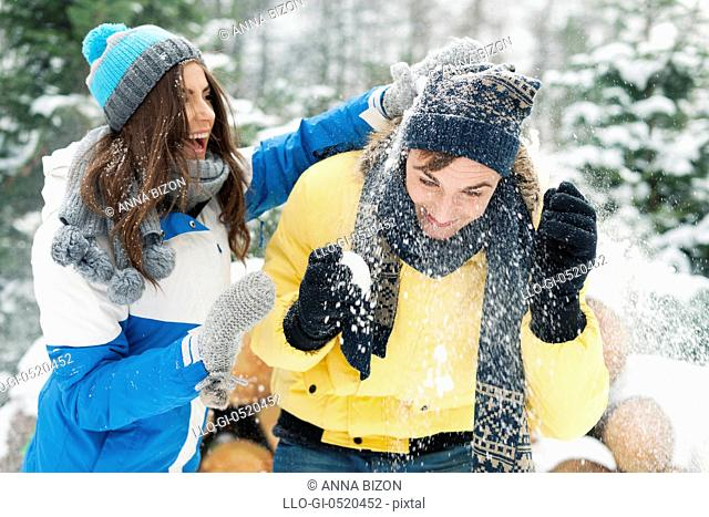 Young couple have fun during the snowball fight. Debica, Poland