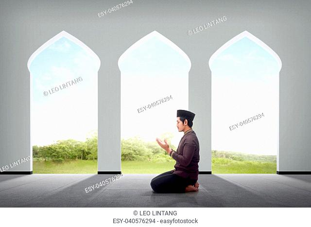 Side view of asian male muslim praying to god inside the mosque