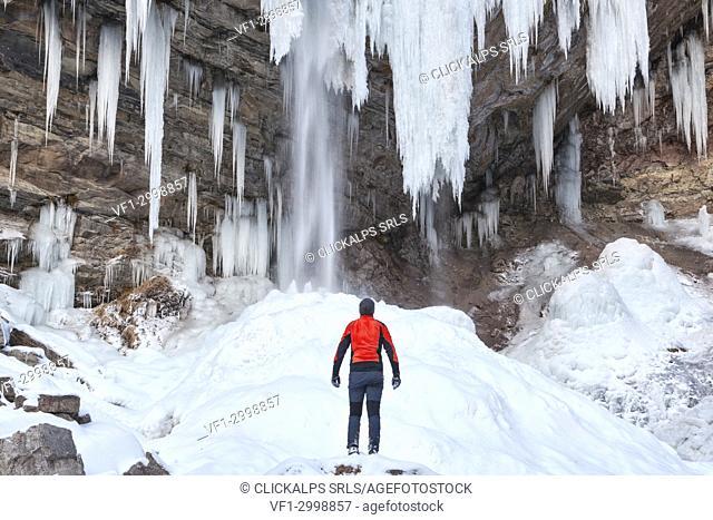 Man in front of Waterfall of Hell (Cascata dell' Inferno) in the San Lucano valley, Taibon Agordino, Belluno, Veneto, Italy