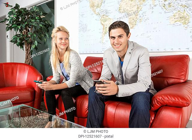 Two young millennial business professionals in the lobby of their workplace using their smart phones while taking a break and one of them looking at the camera;...