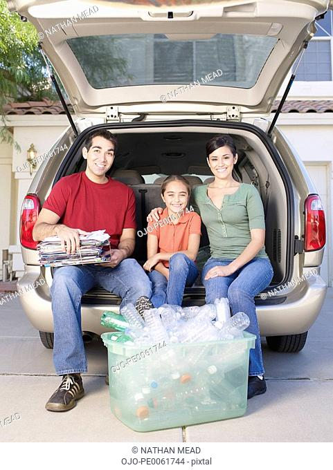 Man with woman and young girl sitting in back of van with bin of recyclable materials smiling