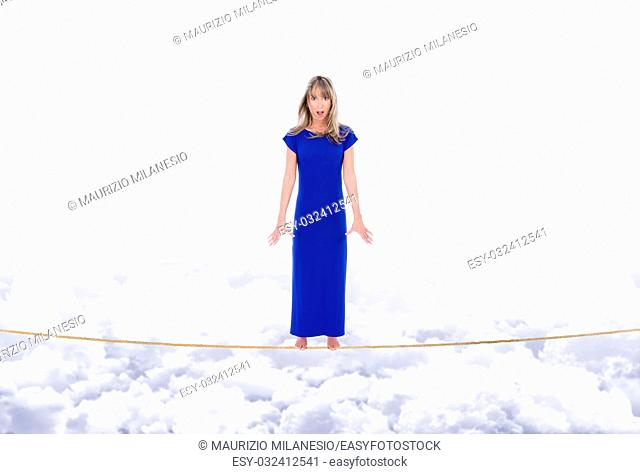 Girl afraid and worried, rocking on the rope stretched out in the sky above the clouds