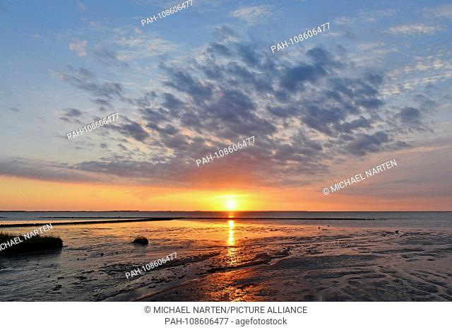 Clouds on the colourful illuminated sky with the rising sun above the Wadden Sea from the island Amrum near the village Nebel, 2 May 2018 | usage worldwide