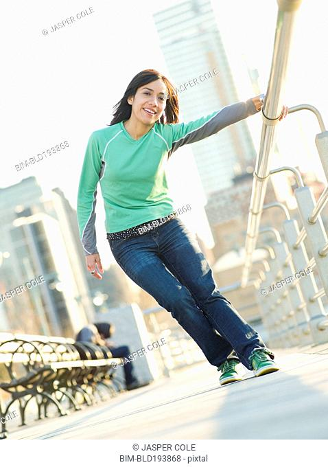 Mixed race woman on pier holding railing