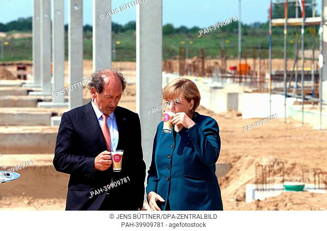 German Chancellor Angela Merkel (R) and CEOof Nestlé Paul Bulcke drink a cup of coffee during the cornerstone laying ceremony for the new Nestlé coffee capsule...