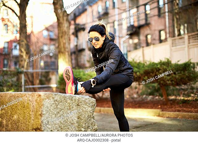 Photograph of a single mid adult female runner stretching in a park in a city