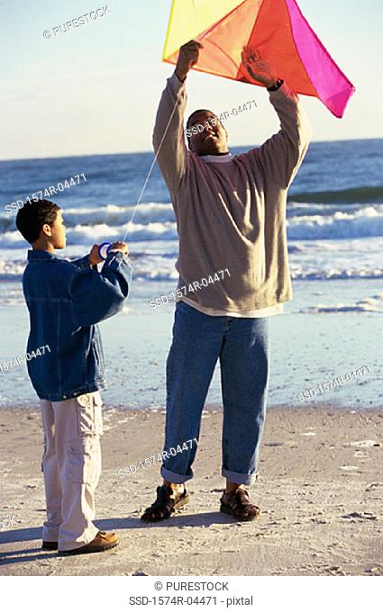 Father and his son flying a kite on the beach