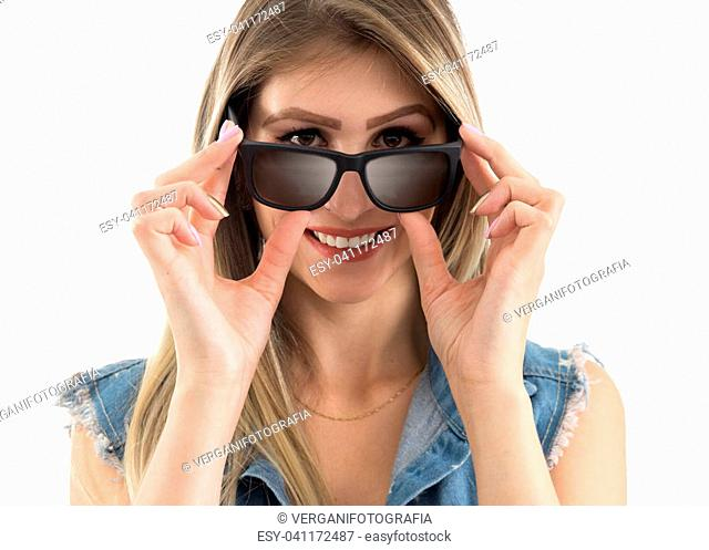 Smiling woman is looking over her sunglasses. Taking off her glasses. He's nice. Beautiful and blonde person wearing jeans vest. White background