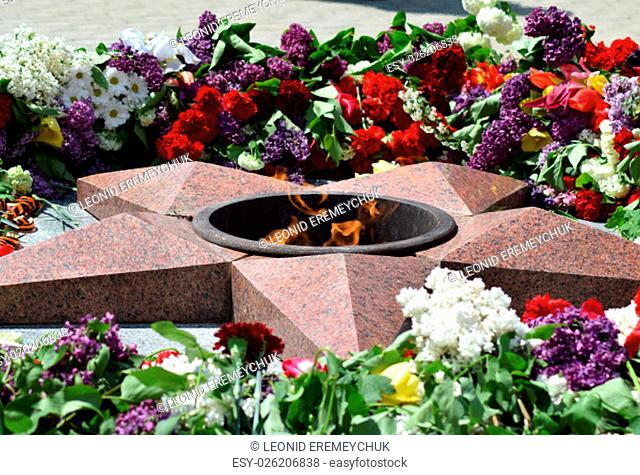 Eternal flame with flowers assigned to it. Celebration of May 9 Victory in the Great Patriotic War