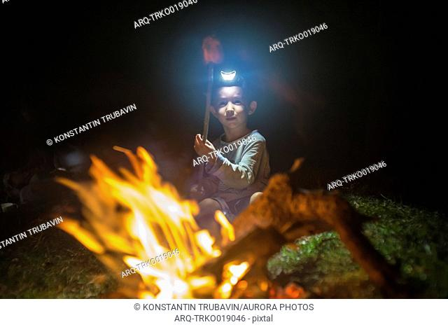 Boy with headlamp sitting and roasting marshmallows in campfire at night