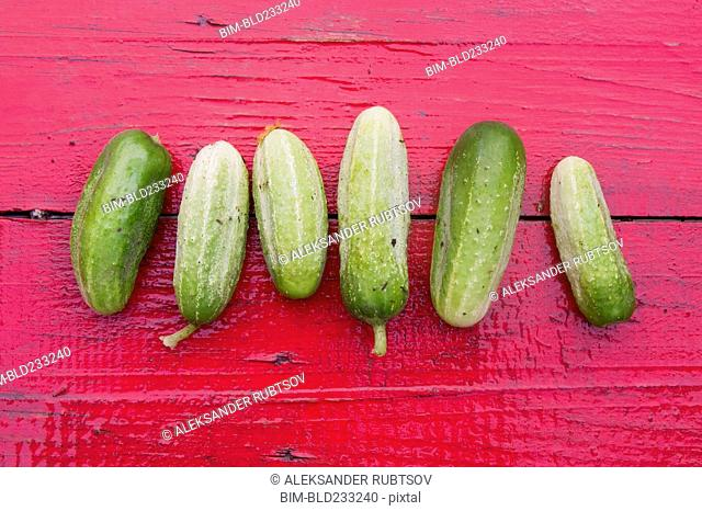 Close up of row of green cucumbers on red wooden table