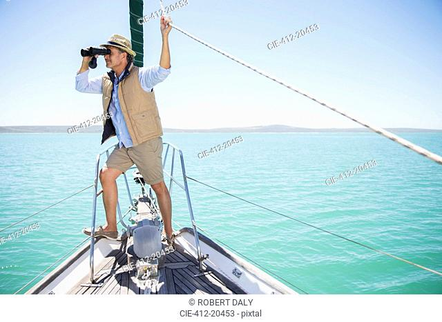 Older man looking out binoculars on edge of boat