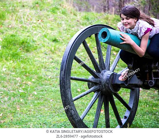 Old fashion brown wheels with green canon in the middle of an old war field with a preteen laying on it and smiling
