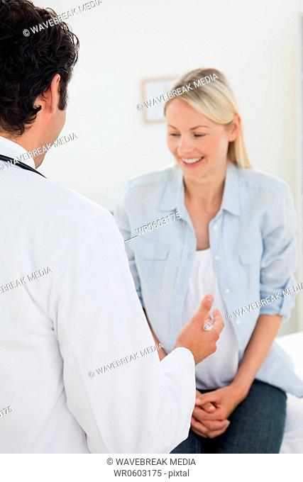 Back view of doctor talking with his smiling patient