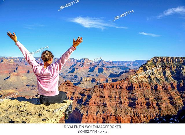 Young woman looking into the distance, happy with outstretched arms, sitting at the precipice of the gigantic gorge of the Grand Canyon, view from Rim Trail