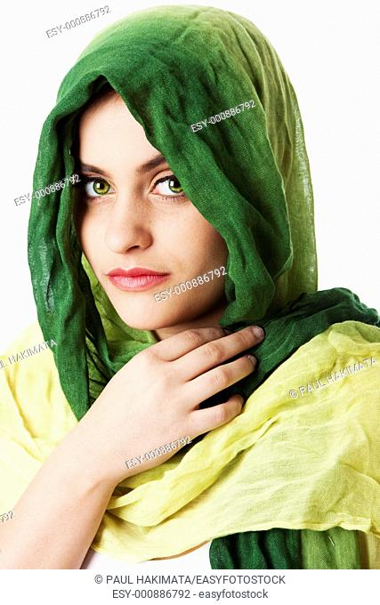 Portrait of mysterious beautiful Caucasian Middle Eastern woman face with green penetrating eyes and green fashion scarf wrapped around head, isolated