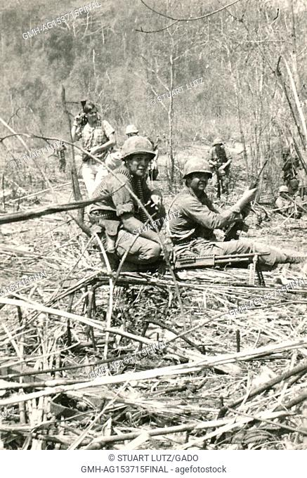 American soldiers with heavy machine guns crouch among plants in the jungles of Vietnam during the Vietnam War, 1968. ()