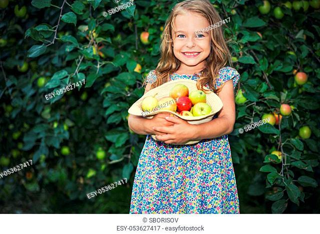 Happy little girl holding apples in the garden