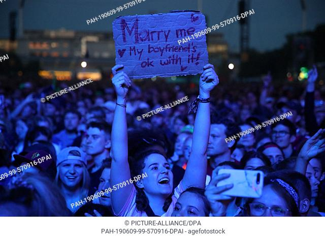 "08 June 2019, Bavaria, Nuremberg: A visitor in the audience of the open-air festival """"Rock im Park"""" holds a sign with the inscription """"Marry me"
