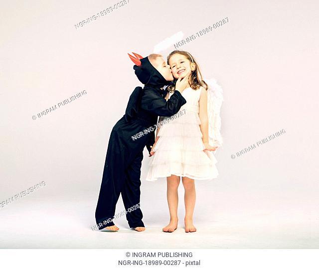 Little devil-boy kissing his angel girlfriend