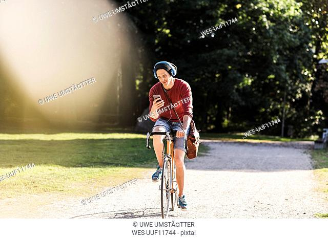 Man on racing cycle looking at cell phone in a park