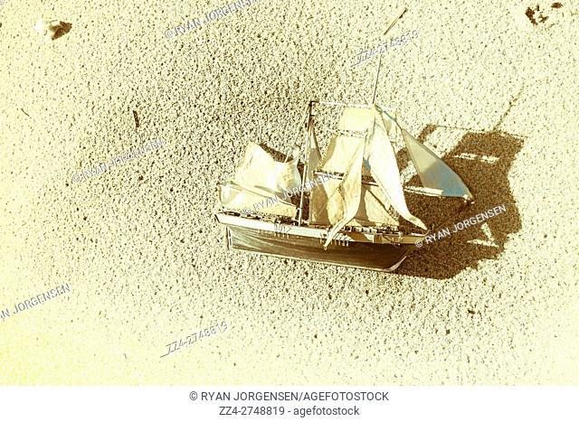 Marine style shipping concept of a cast away model boat left stranded on a deserted beach