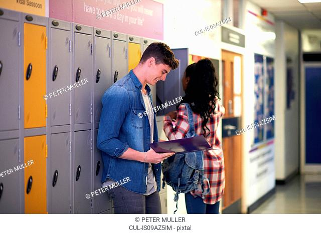 Young male student revising from file in college locker room