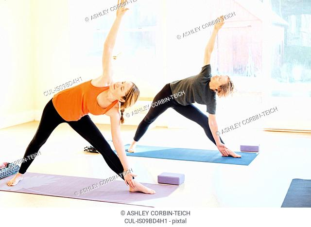 Two women practicing triangle yoga pose (trikonasana) in yoga studio