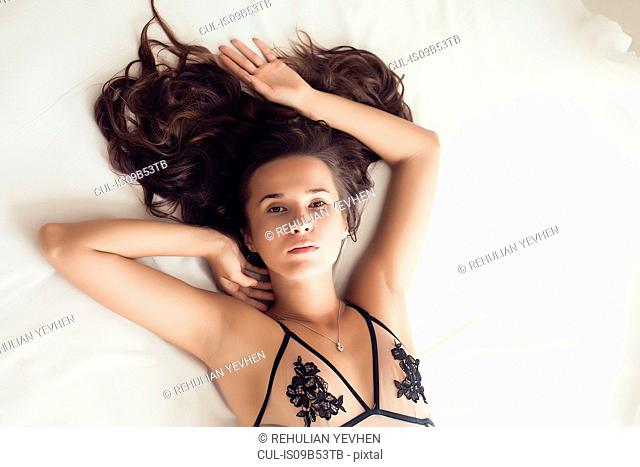 Portrait of young woman wearing swimwear, lying on bed