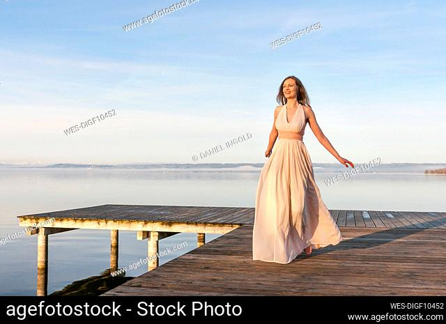 Full length of smiling beautiful woman walking on pier over lake against sky