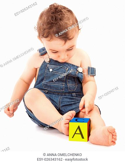 Cute little boy sitting and playing with smart cube isolated on white background, with interest learning letters, happy educational process
