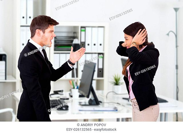 Side view of boss yelling at secretary covering ears in office