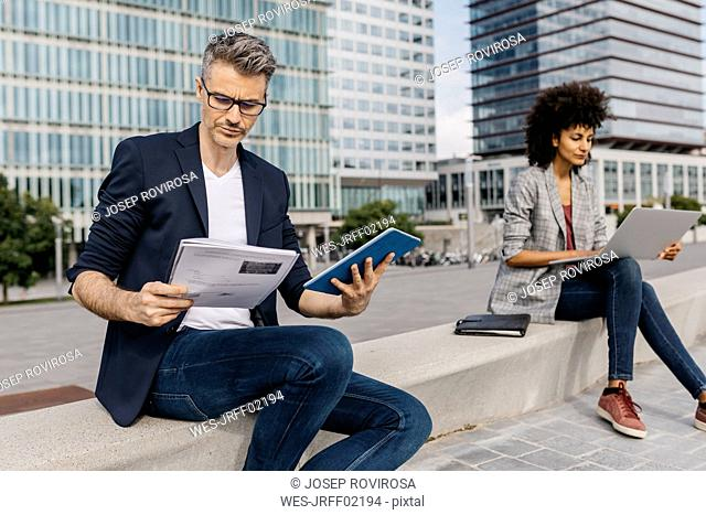 Businessman and businesswoman working outside office building