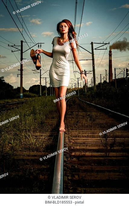 Caucasian woman balancing on train tracks