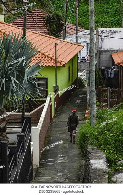 Madeira, Portugal A man walks in a tropical back alley of Canical