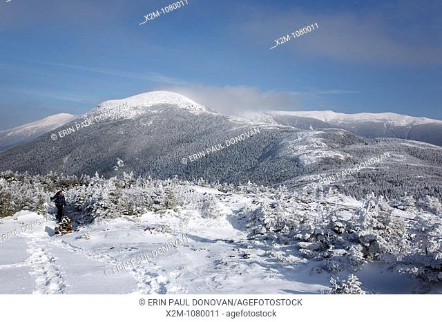 A hiker on the Appalachian Trail near Mount Pierce in the White Mountains, New Hampshire USA  Mount Eisenhower is in the background