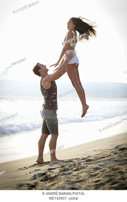 Young man throwing young woman up to catch her - Riviera Nayarit, Mexico
