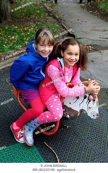 Two girls on rocking horse