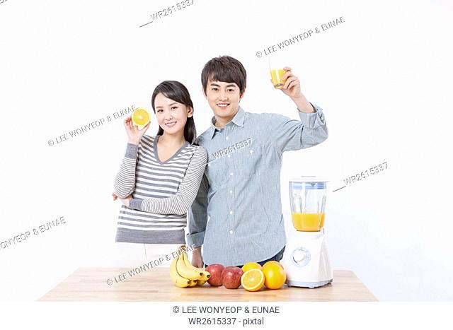 Young smiling couple showing fruit juice