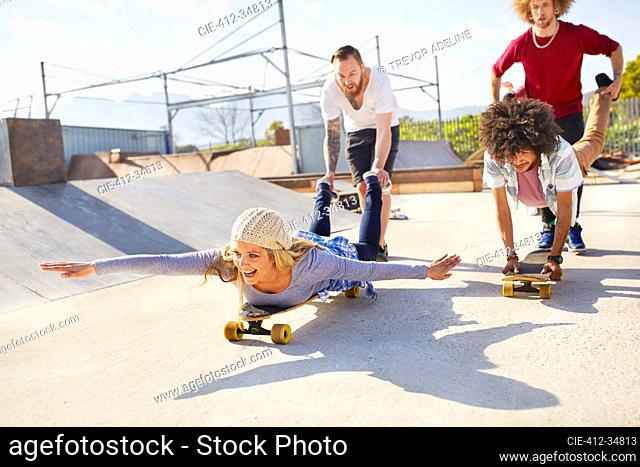 Playful friends on skateboards at sunny skate park