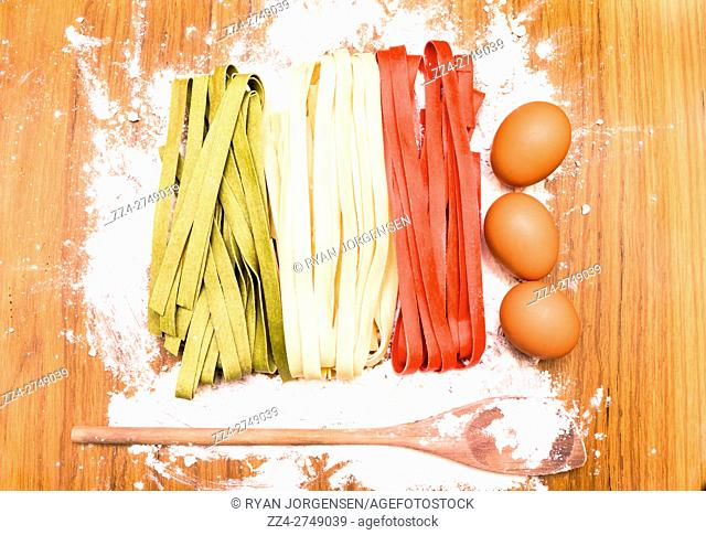 Creative cookery concept - Italy flag made in pasta with eggs and wooden spoon on white flour