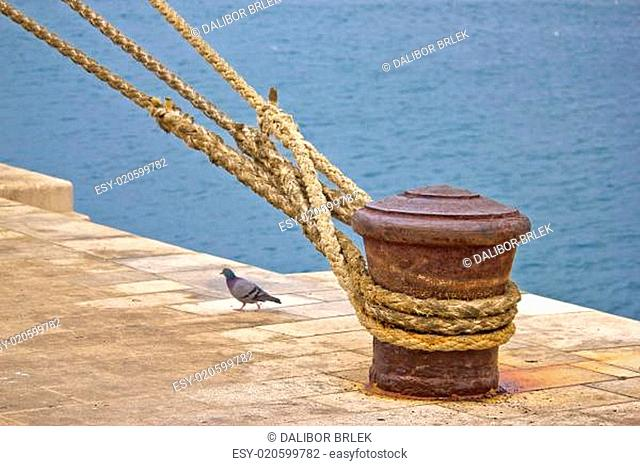 Rusty mooring bollard with ship ropes