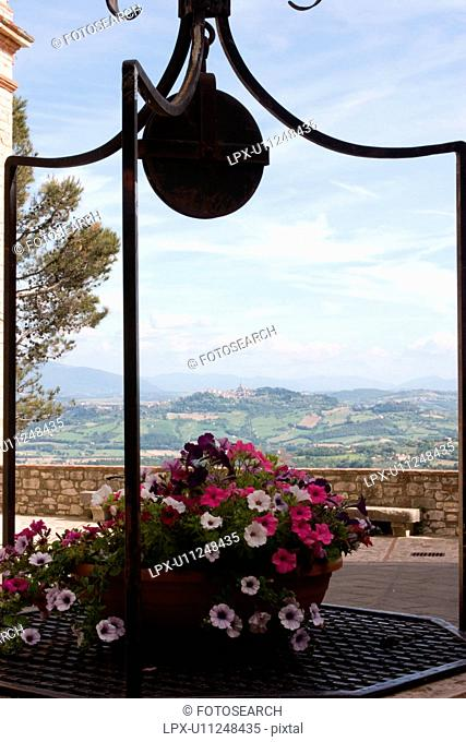 View of Tiber valley with hilltop town of Todi seen beyond medieval well, with wrought iron detail, and flowers, blue sky on sunny summer afternoon