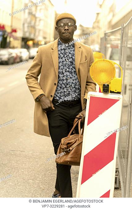 stylish man behind on road sign at street in city Munich, Germany. Streetstyle, male blogger fashion look